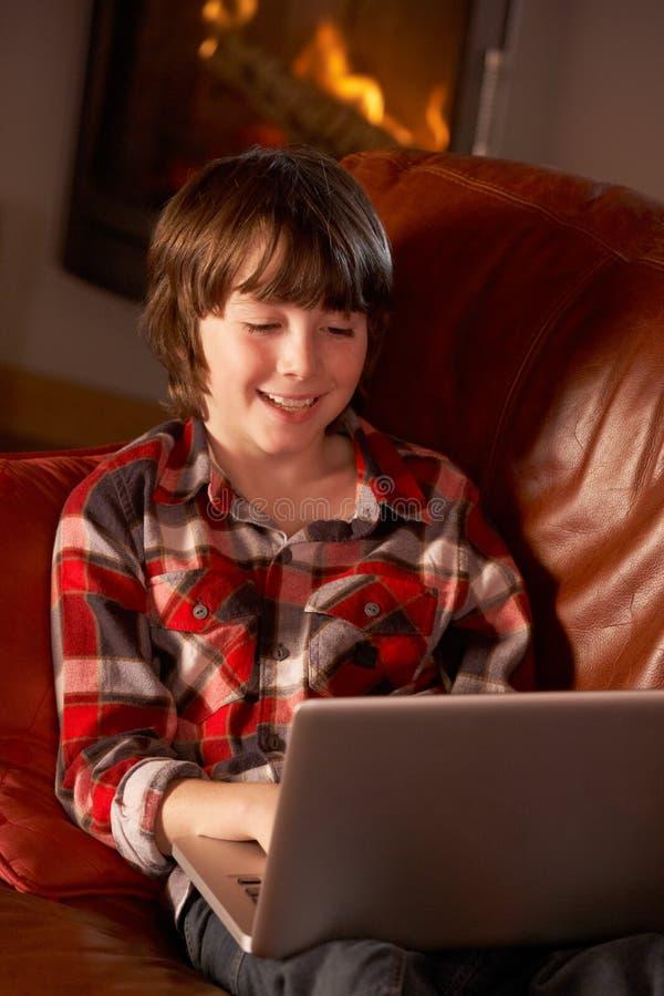 Muchacho joven que se relaja con la computadora portátil por el fuego de registro acogedor fotografía de archivo libre de regalías