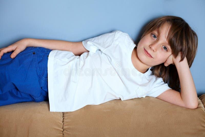 Muchacho joven que se relaja en el sofá fotos de archivo