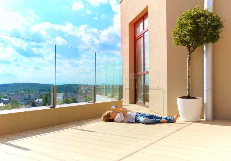 Muchacho joven que se relaja en terraza, en último piso fotografía de archivo