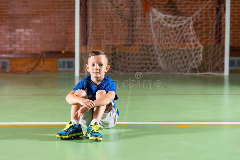 Muchacho joven que se sienta en esperar de tierra foto de archivo