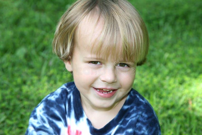 Muchacho joven que se sienta en la hierba imagenes de archivo