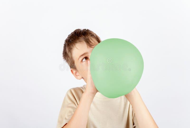 Muchacho joven que sopla un juguete del limo como si fuera un globo imagen de archivo libre de regalías