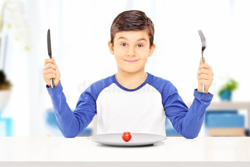 Muchacho joven que sostiene la bifurcación y el cuchillo con el tomate en la placa en o delantero imagenes de archivo