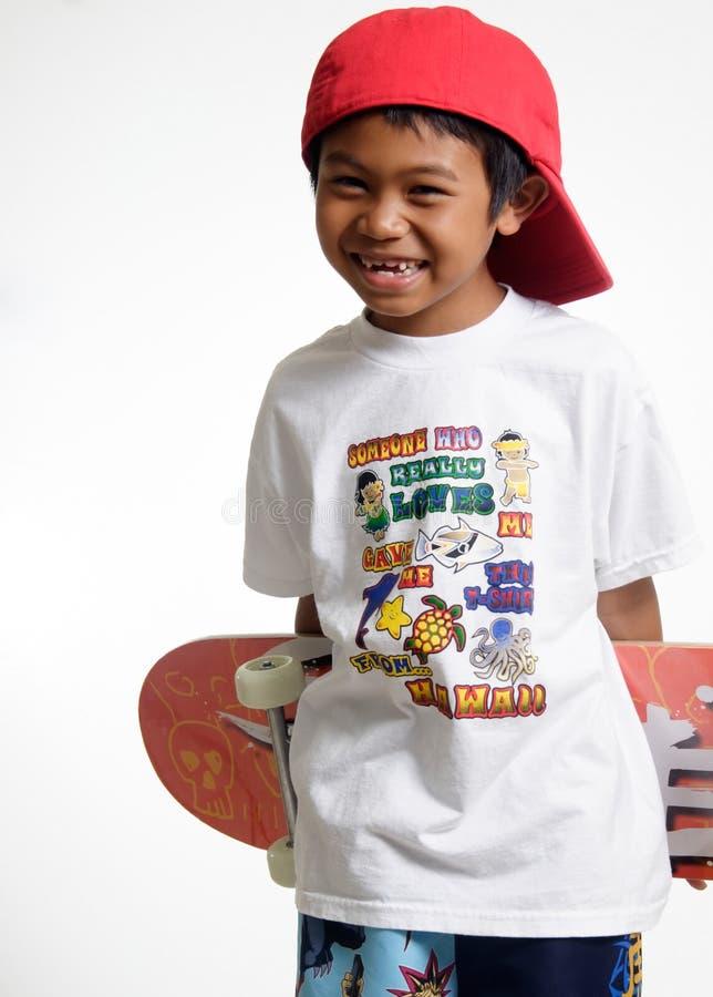 Muchacho joven que sostiene su patín fotografía de archivo