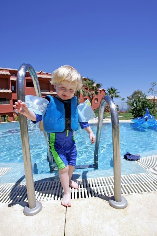 Muchacho joven que sube fuera de piscina el vacaciones fotos de archivo libres de regalías