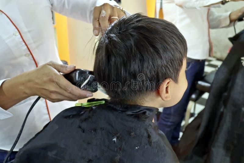 Muchacho joven que tiene un corte de pelo foto de archivo libre de regalías