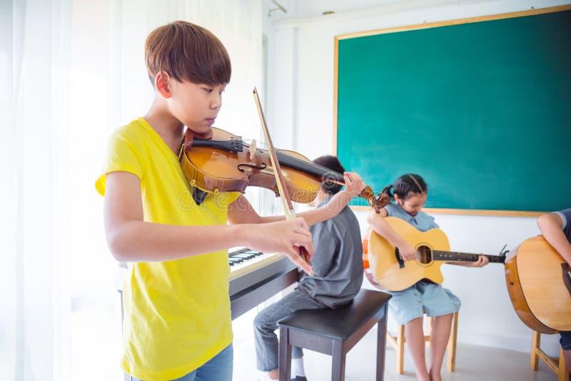 Muchacho joven que toca el violín en sala de clase imagen de archivo