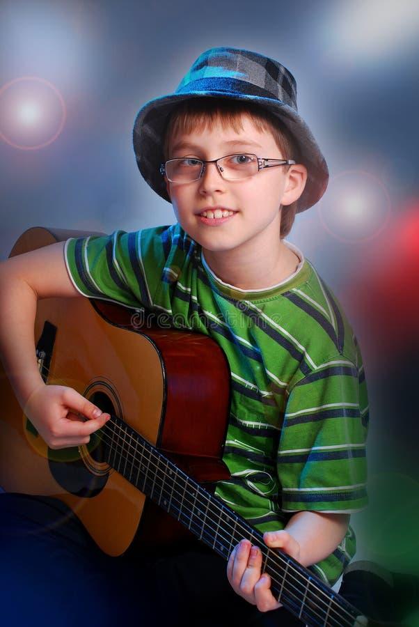 Muchacho joven que toca la guitarra fotografía de archivo