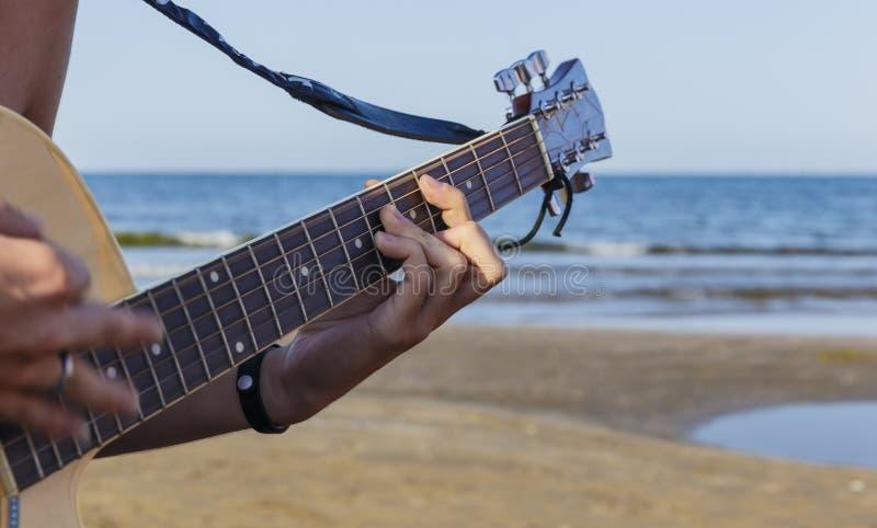 Muchacho joven que toca la guitarra acústica en la playa imagenes de archivo