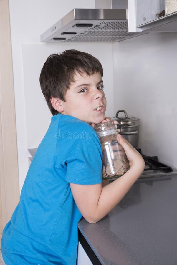 Muchacho joven que toma el caramelo de un alto armario de cocina imagenes de archivo