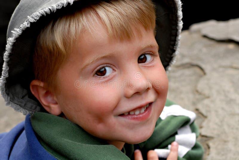 Muchacho joven que toma el sol en una roca fotos de archivo