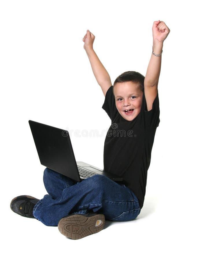 Muchacho joven que trabaja en el ordenador portátil fotografía de archivo