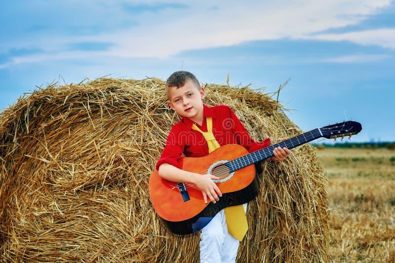 Muchacho joven romántico con la guitarra en el campo foto de archivo libre de regalías