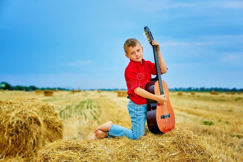 Muchacho joven romántico con la guitarra en el campo imagen de archivo