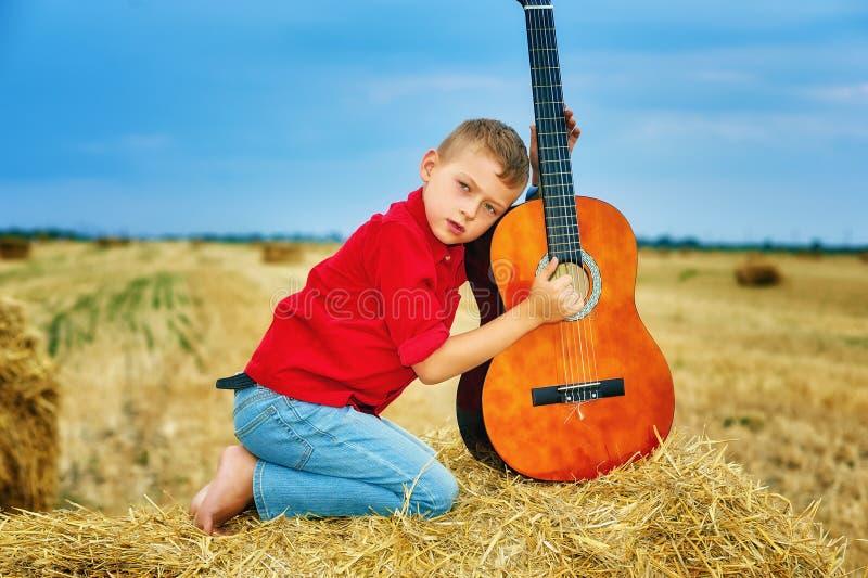 Muchacho joven romántico con la guitarra en el campo imagen de archivo libre de regalías