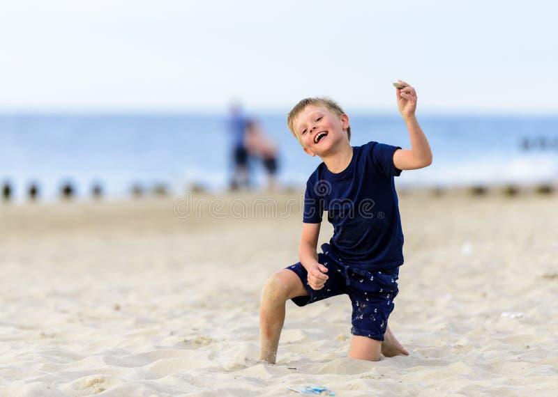 Muchacho joven rubio que goza de una playa fotos de archivo