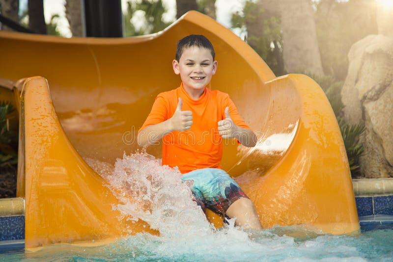 Muchacho joven sonriente montando abajo de mostrar del tobogán acuático los pulgares para arriba fotografía de archivo