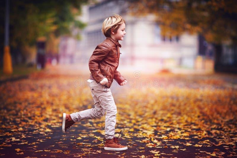 Muchacho joven sonriente, niño que se divierte en parque de la ciudad del otoño entre las hojas caidas fotos de archivo libres de regalías