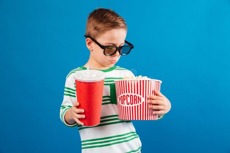 Muchacho joven tranquilo en las lentes que se preparan para mirar la película imagen de archivo