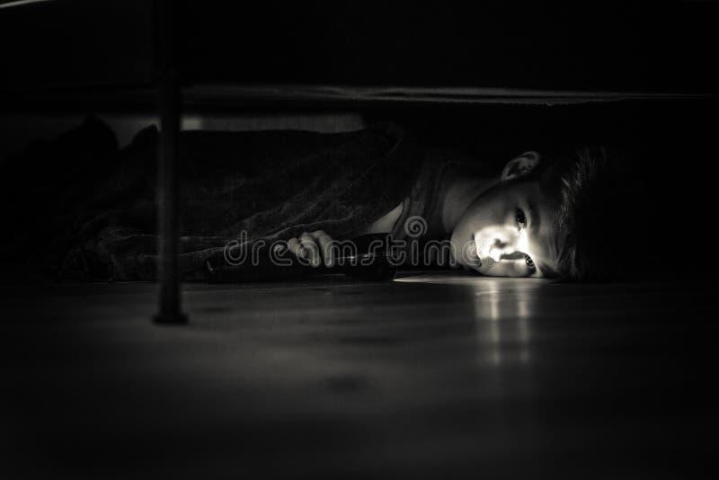 Muchacho joven triste con la linterna que miente debajo de su cama fotografía de archivo