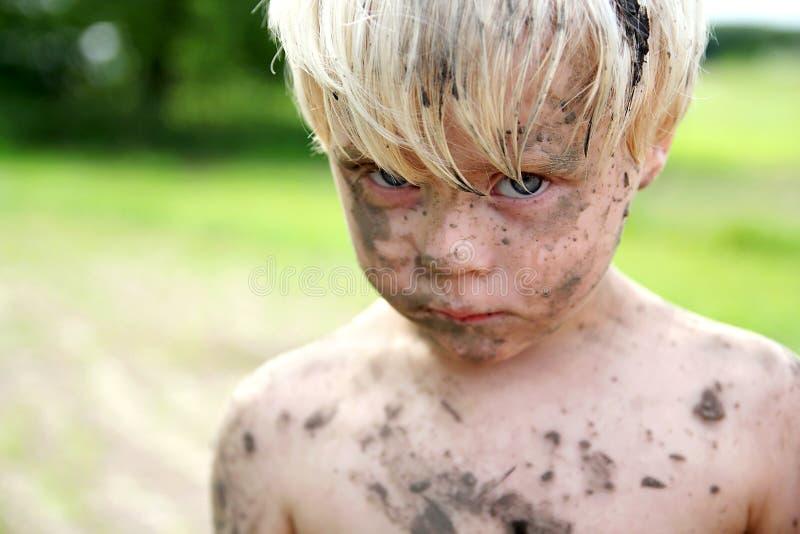 Muchacho joven triste cubierto en suciedad y fango afuera imagenes de archivo
