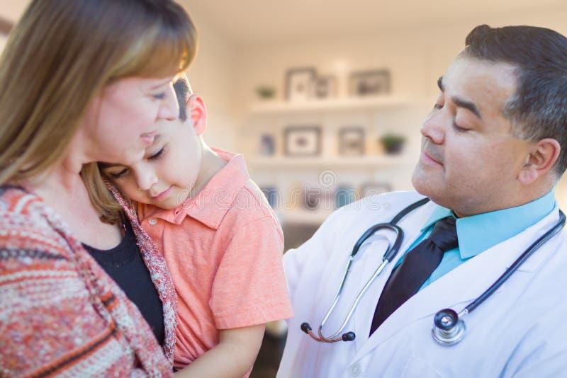 Muchacho joven y madre enfermos que visitan con el doctor hispánico en Offic foto de archivo