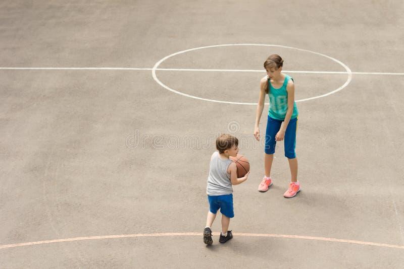 Muchacho joven y muchacha que juegan a baloncesto foto de archivo