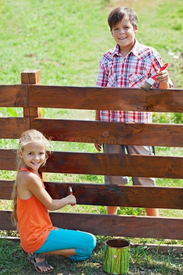Muchacho joven y muchacha que pintan una cerca de madera imagen de archivo libre de regalías