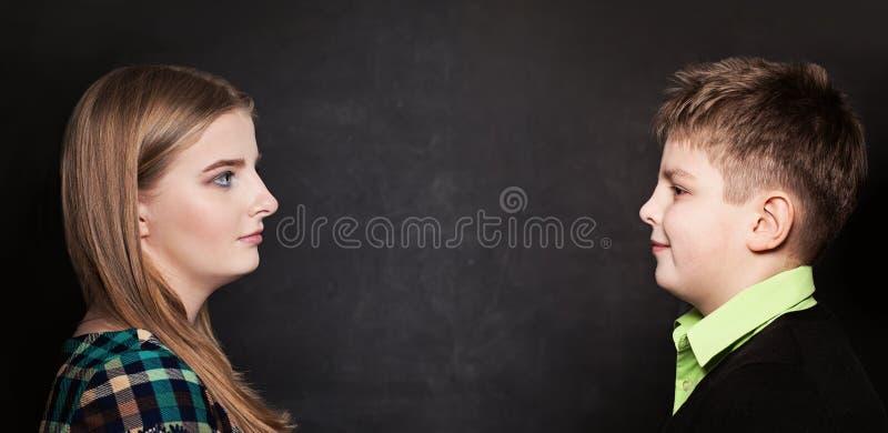Muchacho joven y muchacha que se miran en fondo de la pizarra fotos de archivo