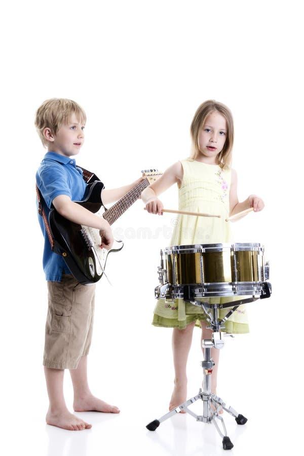 Muchacho joven y muchacha que tocan los tambores y la guitarra fotos de archivo