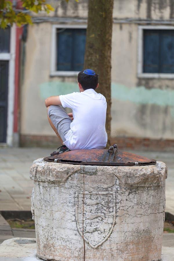 Muchacho judío en Kippah que se sienta en un pozo viejo en Campo de Ghetto Novo, Venecia, Italia fotografía de archivo libre de regalías