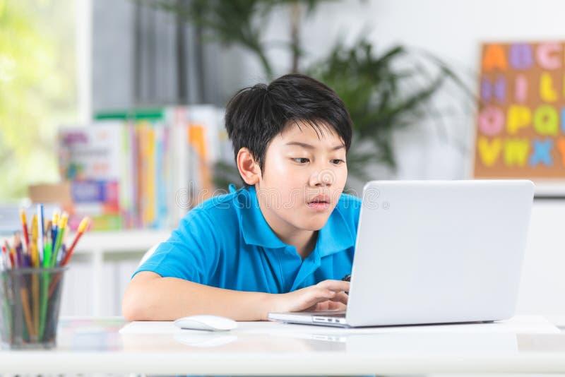 Muchacho lindo asiático que usa el ordenador portátil imágenes de archivo libres de regalías