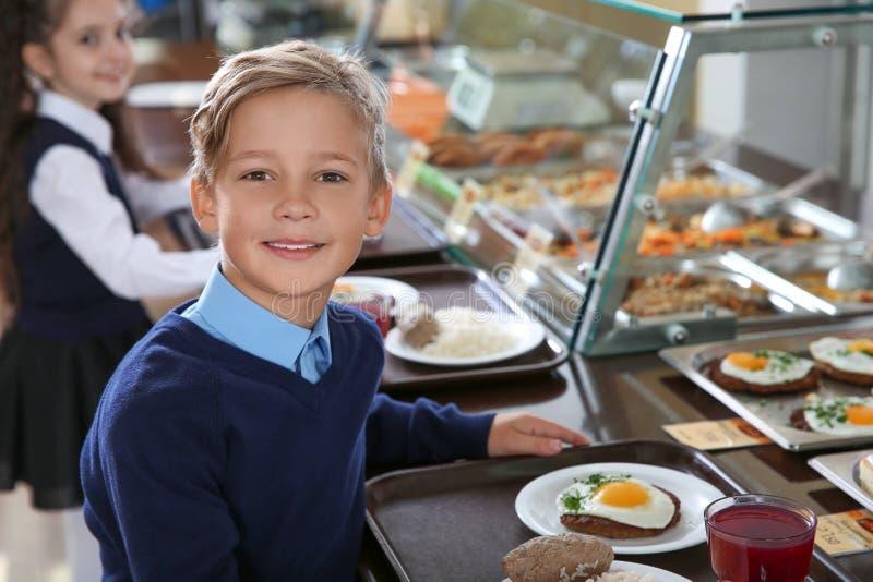 Muchacho lindo cerca de la línea de servicio con la comida sana en cantina imagen de archivo