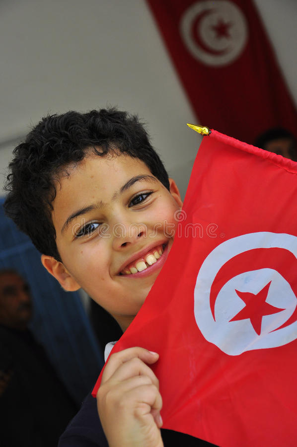 Muchacho lindo con el indicador tunecino rojo fotos de archivo libres de regalías
