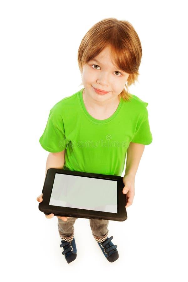Muchacho lindo con el ordenador de la tableta imagenes de archivo