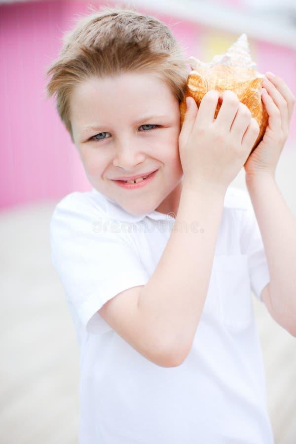 Muchacho lindo con el seashell fotos de archivo