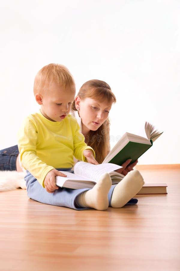 Muchacho lindo con la madre que lee un libro imagenes de archivo