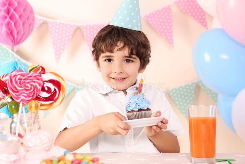 Muchacho lindo con la magdalena que celebra cumpleaños en casa fotografía de archivo libre de regalías