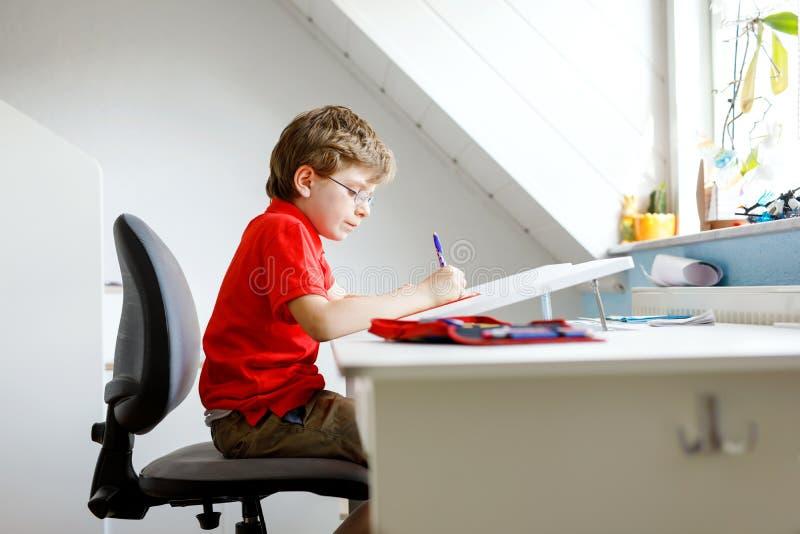 Muchacho lindo del niño con los vidrios en casa que hacen la preparación, escribiendo letras con las plumas coloridas foto de archivo