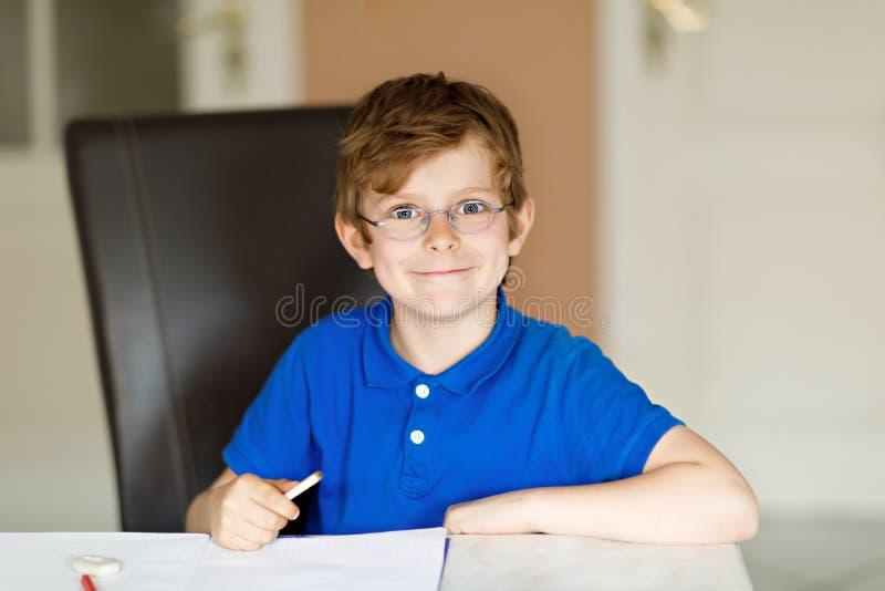 Muchacho lindo del niño con los vidrios en casa que hacen la preparación, escribiendo letras con las plumas coloridas imagenes de archivo