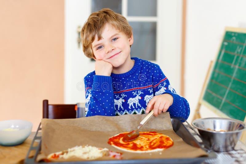 Muchacho lindo del niño que hace la pizza italiana con las verduras frescas foto de archivo libre de regalías