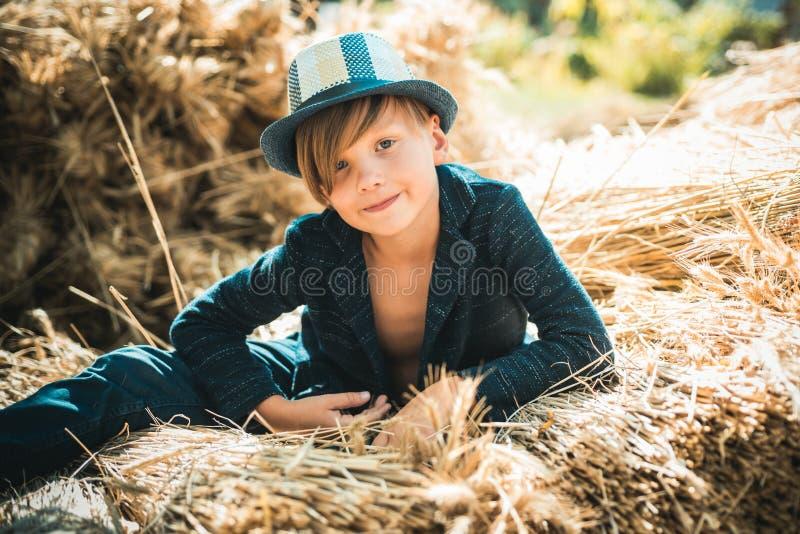 Muchacho lindo del pequeño niño que sostiene la hoja de oro en fondo del pueblo de la granja El muchacho del niño miente en el he imagen de archivo libre de regalías