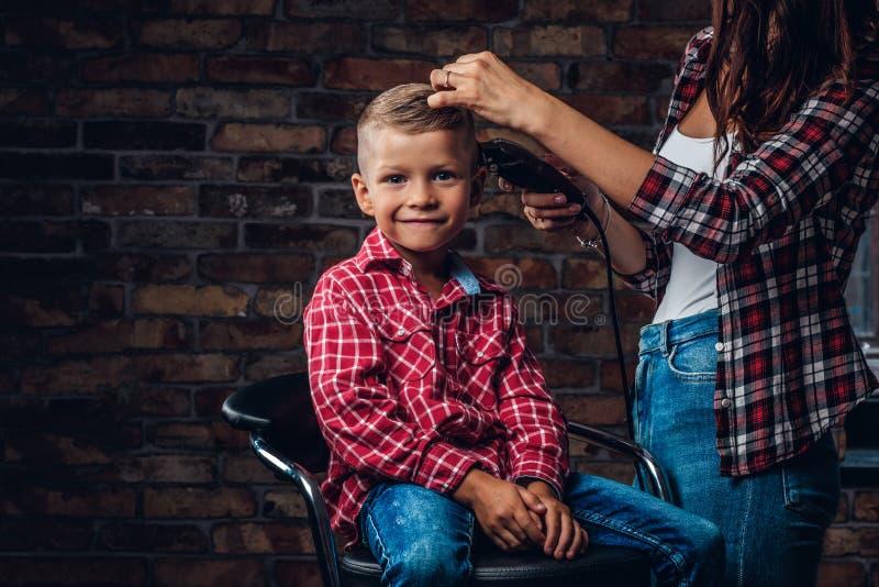 Muchacho lindo del preescolar que consigue corte de pelo El peluquero de los niños con el condensador de ajuste está cortando al  imágenes de archivo libres de regalías