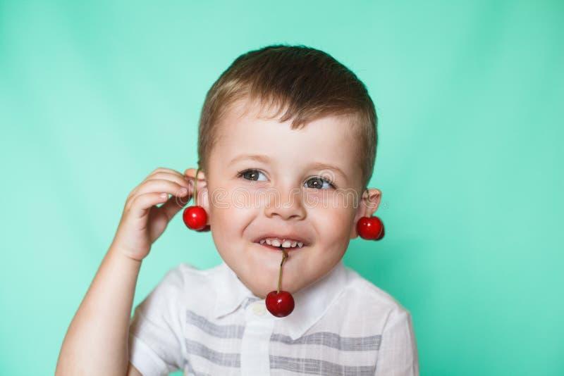 Muchacho lindo del muchacho que come cerezas maduras, haciendo caras divertidas y jugando con las cerezas, divirtiéndose imagenes de archivo