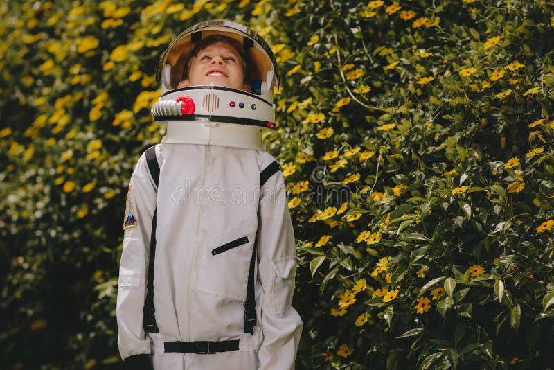 Muchacho lindo en el vestido del astronauta que juega al aire libre imagen de archivo libre de regalías
