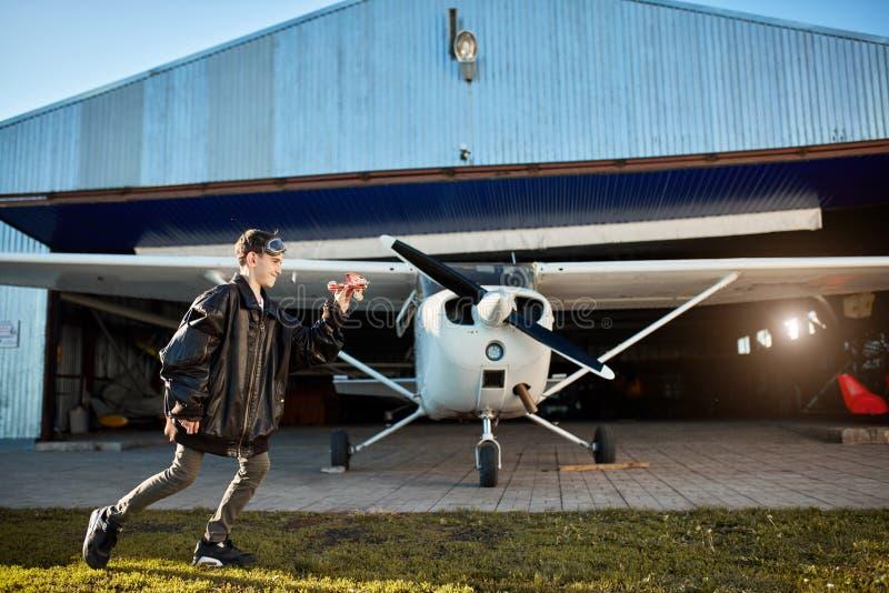 Muchacho lindo en la chaqueta de cuero del padre grande que juega fuera de hangar con el aeroplano del juguete foto de archivo