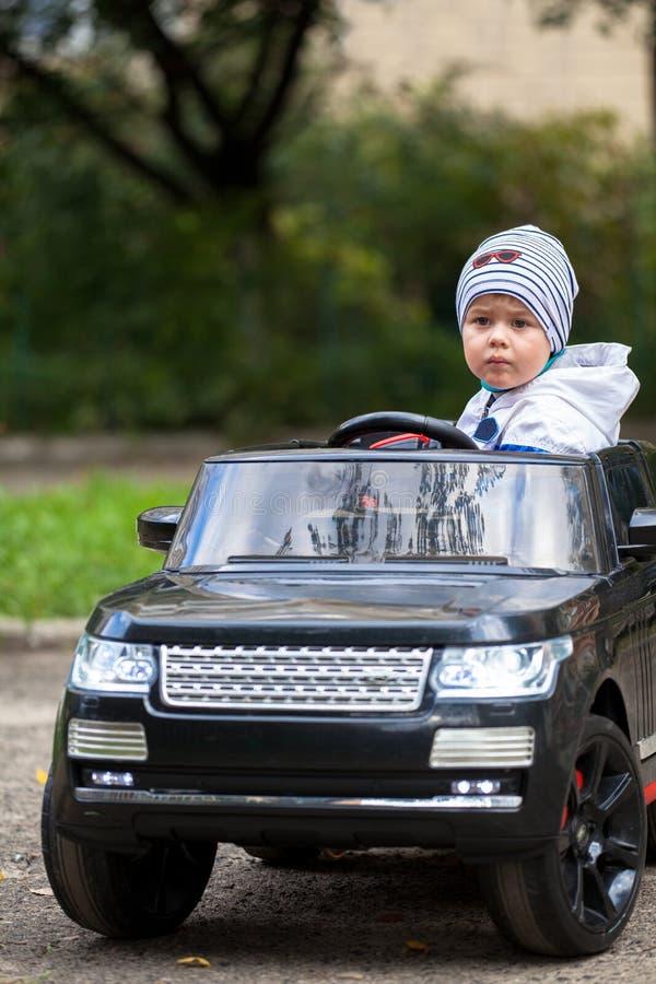 Muchacho lindo en montar un coche eléctrico negro en el parque fotos de archivo libres de regalías