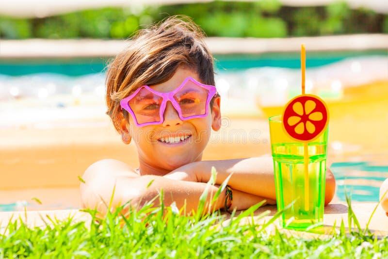 Muchacho lindo en piscina con la bebida de restauración imagen de archivo