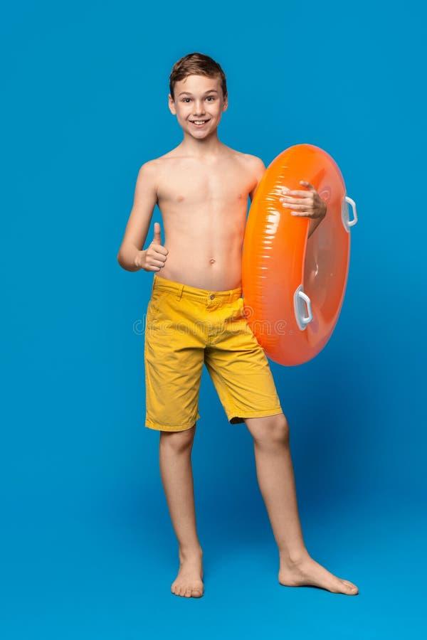 Muchacho lindo en pulgar de la demostración del traje de baño para arriba, llevando a cabo el anillo inflable anaranjado fotografía de archivo libre de regalías