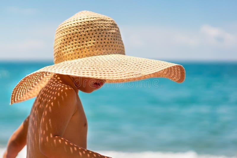 Muchacho lindo en un sombrero de paja en la playa foto de archivo libre de regalías